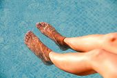 Nice legs of woman soaking feet in swimming pool