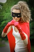 Blond masked girl ready to fight wearing a red cape and red gloves