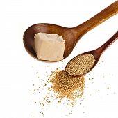 baking ingredient yeast powder in wooden spoon on white background