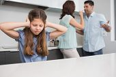 Sad young girl covering ears while parents quarreling in the kitchen at home