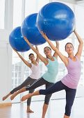 Happy fitness class and instructor doing pilates exercise with fitness balls in bright room