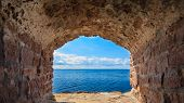picture of stonewalled  - View of blue sea and sky from hole in old stonewall wall - JPG