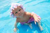Baby Girl In Hat Sitting In Waterpool