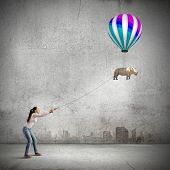 Young woman in casual and rhino flying in sky