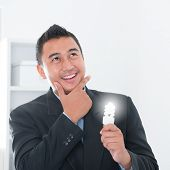 Southeast Asian businessman holding an illuminated light bulb, thinking in office.