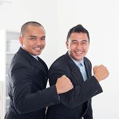 Southeast Asian business men celebrating success in office.