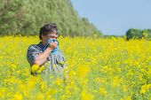 stock photo of hay fever  - man in field blowing his nose and suffering from hay fever - JPG