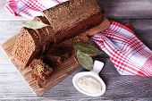 Fresh homemade bread on napkin, on color wooden background
