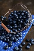 Delicious blueberries in wicker basket on table close-up