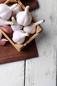 Fresh garlic in box, on wooden background