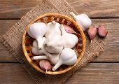 Fresh garlic in wicker basket, on wooden background