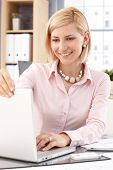 Happy blonde, smiling, casual caucasian businesswoman with laptop computer at business office. Close