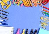 School supplies arranged on the outer edge of a blue background. Center is blank for your own copy.