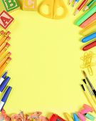 School supplies arranged on the outer edge of a yellow background. Center is blank for your own copy.