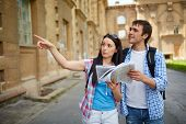 Couple of young travelers with map sightseeing in ancient town