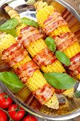 Grilled bacon wrapped corn on table, close-up