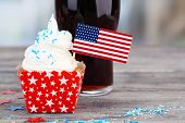 American patriotic holiday cupcake and glass of cola on wooden table