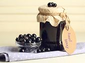 Ripe blackcurrants in bowl and glass jar with tasty jam on light wooden background.