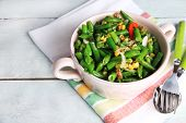 Salad with green beans, ham and  corn in bowl, on color wooden background
