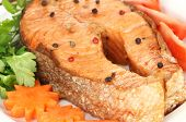 Appetizing grilled salmon with lemon and vegetables close up