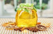 Jar of honey and dried lemon slices on bright background