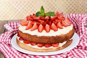Delicious biscuit cake with strawberries on table on beige background