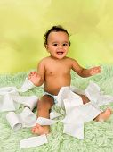 Adorable african baby boy playing with toilet paper