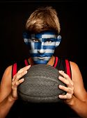 portrait of basketball player with greek flag painted on his face