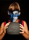 portrait of basketball player with finish flag painted on his face