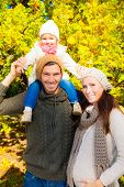 family in autumn park smiling