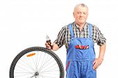 Mature mechanic standing by a bicycle wheel and holding pliers isolated on white background