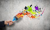 Close up of hand holding brush with colorful paint splashes
