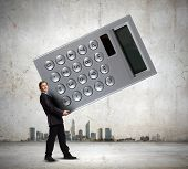 Young businessman in suit carrying big calculator