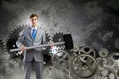 Young determined businessman with hammer and cogwheels at background