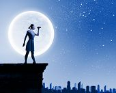 Silhouette of woman looking in binoculars with big full moon at background