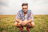 serious crouched casual man in a field of grass looks to the camera