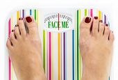 image of eat me  - Feet on bathroom scale with words  - JPG