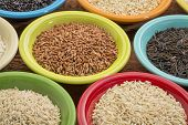 a variety of rice grains on colorful ceramic bowls against a grained wood