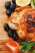 baked meat : homemade turkey with black olives and raw tomatoes on wooden board isolated over white