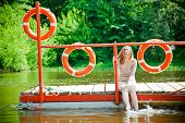 image of wet feet  - young woman wetting her feet in the river sitting on a platform - JPG