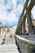 Tourist Climb On Ancient Aqueduct Of Segovia