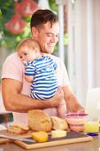 Father Holding Baby And Making Snack Whilst Using Laptop