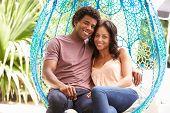 Couple Relaxing On Outdoor Garden Swing Seat