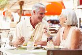 Senior Couple Enjoying Lunch In Outdoor Restaurant