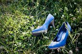 High heel blue suede shoes in grass