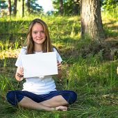 Lovely teengirl holding clean white sheet paper, in the park (banner for your message)