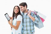 Attractive young couple with shopping bags and tablet pc on white background