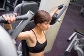 Focused brunette using weights machine for arms at the gym