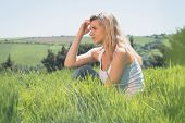 Pretty blonde thinking and sitting on grass on a sunny day in the countryside