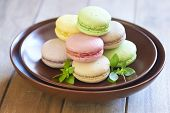 Colorful macaroons on brown plate